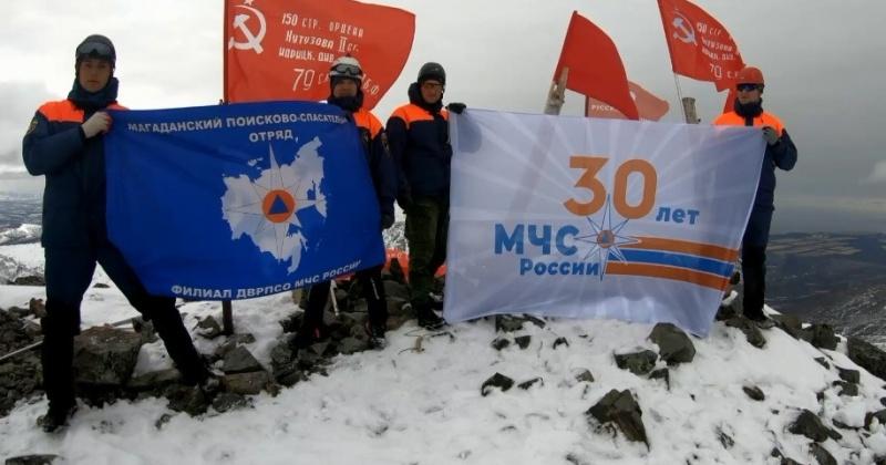 Спасатели Магадана развернули Знамена Победы и флаг 30-летия МЧС на горе Комендант